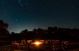 a fire is surrounded by chairs under a starry night sky