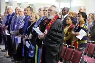 UU ministers gathered together in worship at an annual meeting.