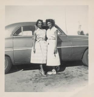 In a square, vintage black & white photo, two Black women pose in front of a car.