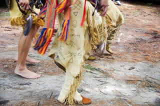 The feet and legs of several members of the Narragansett tribe, in traditional dress, at their 2012 pow-wow.