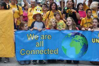 "UUs of all ages stand behind a banner with a picture of the earth, reading ""We are all connected."""