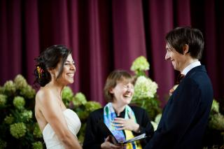 A Unitarian Universalist minister shares a laugh with a couple during their wedding ceremony.
