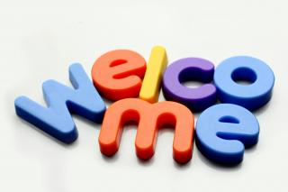 "refrigerator magnets on a flat surface jumble together to spell ""welcome"""