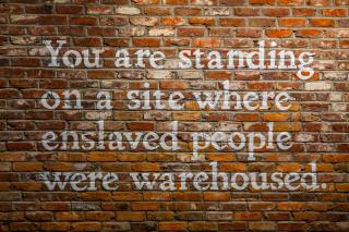 "Picture of a brick wall on which is painted ""You are standing on a site where enslaved people were warehoused."""