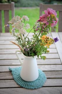 a white pitcher on a table outdoors holds a tangle of pink, white, and gold wildflowers