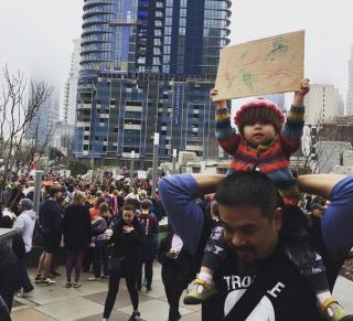 At the Women's March in Charlotte, NC, January 21, 2017, a toddler sits atop her father's shoulders holding up a scribbled protest sign.