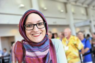 A young UU woman in a headscarf smiles.