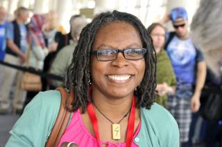 A woman with small square glasses, dreadlocks, and a flaming chalice necklace smiles.