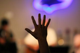Over an out-of-focus background of musicians on a chancel, a single hand is raised in praise, fingers spread