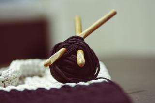 Two wooden knitting needles plunged into a ball of thick purple yarn