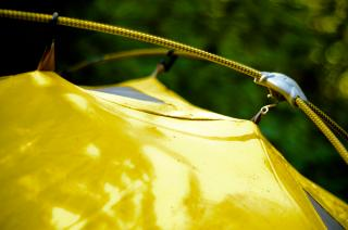 A close-up of the side of a bright yellow tent, with its fabric hung from taught tent poles.