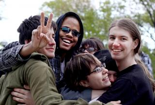 A group of smiling young adults hug.