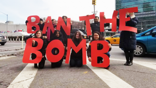 "Protesters outside the United Nations urging the General Assembly members to vote to ""Ban the Bomb"""