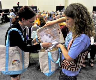 two ushers put the special collection in tote bags during 2013 GA plenary