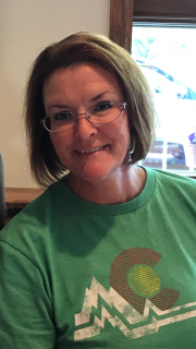 White woman with short red hair and glasses smiling and wearing a green t-shirt