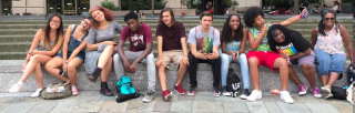 several youth of varying racial identities and genders sit on a bench, some looking serious, some being silly