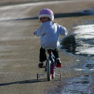 child riding a bike with training wheels looking backwards