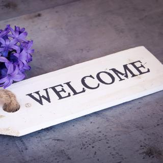 Welcome on a wooden tag attached to a hyacinth