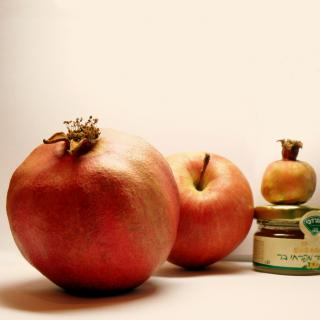 An apple, two pomegranates, and a small jar of honey with a label printed in Hebrew.