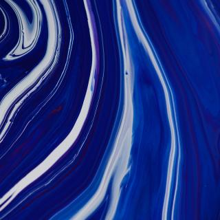 close up - flowing bright blue paint, white reflections on the ridges