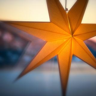 A glowing paper star lantern appears to hang in a window, with a winter scene outside.