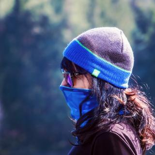 Woman outdoors with wool hat, mask and sunglasses