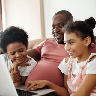 a Black parent sits in front of a laptop with his two children