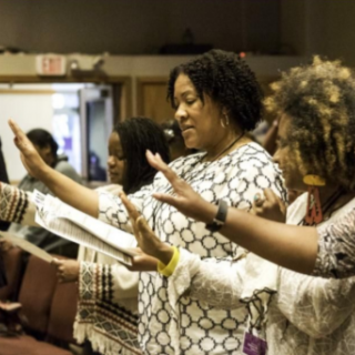 Black women raising their hands in worship