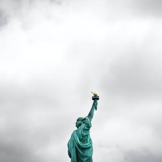 The Statue of Liberty, as seen from behind and from the waist up, against a grey sky.