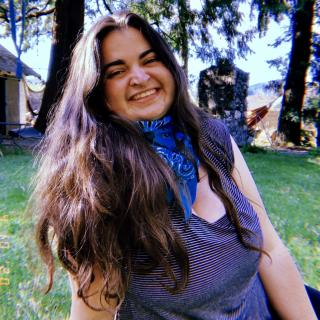 Martha smiles while sitting on the ground, green grass around her, and a blue bandana tied around her neck.