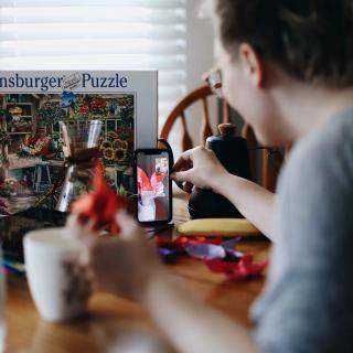 A person in a gray shirt is doing a jigsaw puzzle, holding up a piece to someone else on a video call on a cell phone.