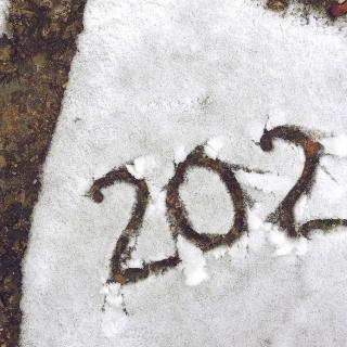 """2021"" is written in the snow on a gravel surface outdoors."