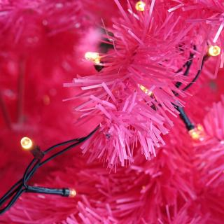 A string of Christmas lights rests on bright pink branches of a Christmas tree that's obviously artificial.