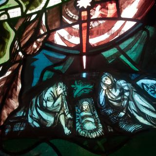 A close-up of a stained glass panel, in reds and greens, depicting Joseph and Mary reclining next to a manger holding Jesus