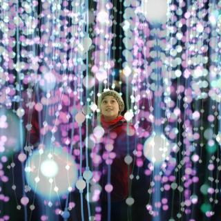 a child smiles up in wonder amid multiple vertical strings of light