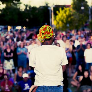 A Black woman, with her back to the camera, speaks into a microphone in front of a large audience outdoors, which appears to be a rally or protest.