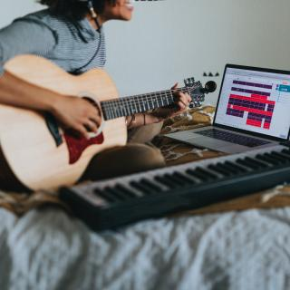 Sitting cross-legged on a bed, a person holds a guitar and appears to sing. Next to them is a musical keyboard and an open laptop.