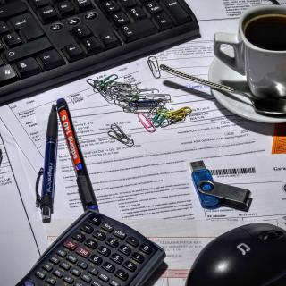 Image of forms on a desk with paper clips, coffee, computer, and other implements.