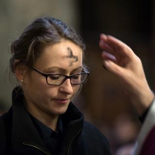 A woman slighty bows her head as a priest's hand moves away, having just left a cross of ashes on her forehead.