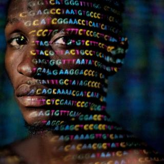 A black man in a dark space looks sideways into the camera. Across his face, in colored light, the letters A G C T represent DNA nucleotides.