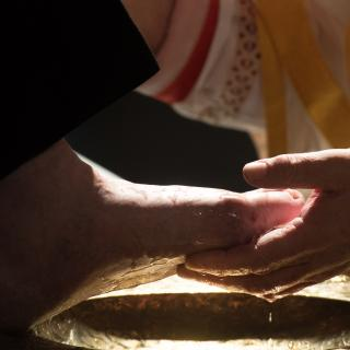 A hand cupping a person's foot in the process of footwashing during a Maundy Thursday Mass.