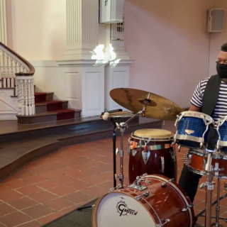 Man with a facemask playing a drum set in a church sanctuary.