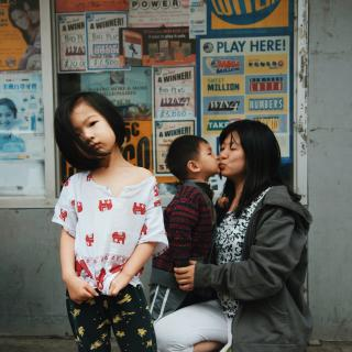 Two children and one adult who appear to be of Asian descent are pictured, one child stands in foreground and the other kisses the adult in the background