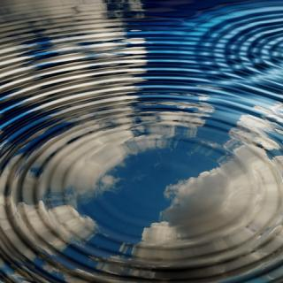 Water with concentric waves reflecting clouds