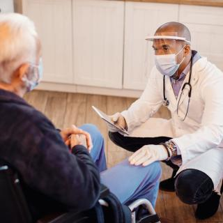 A Black health care provider, in face mask and shield, squats to talk with a man in a wheelchair, who also wears a facemask.