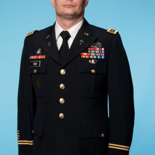 George Tyger stands against a blue background in his dress uniform, which includes many military insignia.