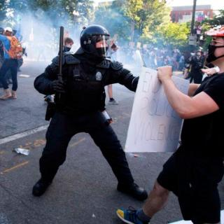 "A protestor holding a sign reading ""End Racist Police Violence"" confronts a police officer in riot gear holding an upraised police baton"