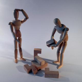 Two wooden people try to put together 3-D wooden puzzle