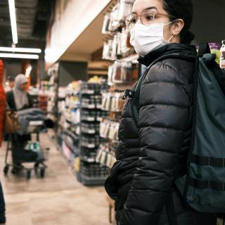 In a grocery store, a person wearing a mask looks off-camera while two other masked shoppers shop behind them
