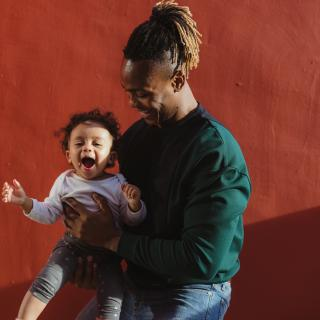 Against a vibrant, deep red wall, a Black parent cradles and smiles down at a happy toddler.